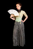 Girl in Victorian dress waving a fan. Girl in Victorian dress with a fan in her hand looking in the camera on a black background royalty free stock image