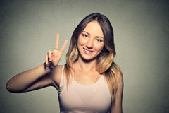 Girl With Victory Sign isolated on gray wall background Royalty Free Stock Photos