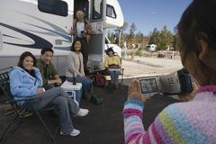 Girl videotaping family outside of RV Stock Photo