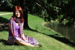 Girl in viloet at grass. In garden Stock Image