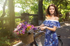 Girl with a vintage bicycle and a basket of flowers stock photo