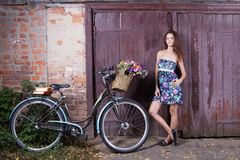 Girl with a vintage bicycle and a basket of flowers stock images
