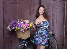 Girl with a vintage bicycle and a basket of flowers royalty free stock photo