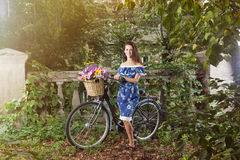 Girl with a vintage bicycle and a basket of flowers Royalty Free Stock Photos