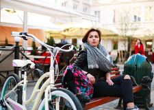 Girl with vintage bicycle sits thoughtfully in old town square Royalty Free Stock Image