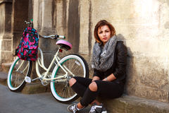 Girl with vintage bicycle sitting by wall of ancient building Royalty Free Stock Photos