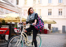 Girl with vintage bicycle on streets of old town square Royalty Free Stock Photos