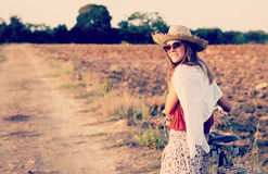 Girl with vintage bike in a country road Royalty Free Stock Photos