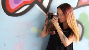 Girl with vintage camera against the graffiti wall and photographs. stock video