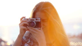 Girl with a vintage camera. Beach, sunset, wind. Waves her hair stock footage