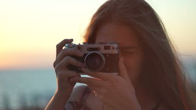Girl with a vintage camera. Beach, sunset, wind. Waves her hair stock video