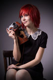 Girl with vintage camera on a chair Stock Image