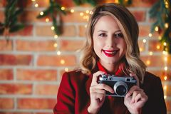 Girl with vintage camera at Christmas lights background. Portrait of a young girl in red coat with vintage camera at Christmas lights background royalty free stock photography