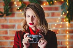 Girl with vintage camera at Christmas lights background. Portrait of a young girl in red coat with vintage camera at Christmas lights background stock photography