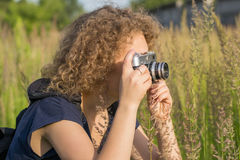 The girl with vintage camera is standing in the tall grass Royalty Free Stock Images