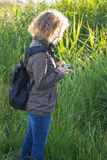 The girl with vintage camera is standing in the tall grass Royalty Free Stock Photos