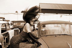 Girl at vintage car. Girl beside vintage car with flapping hairs stock photos