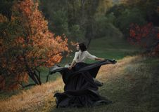 A girl in a vintage dress. Is spinning on a hill. Background wild nature. Taste of freedom. Artistic Photography Royalty Free Stock Photo