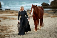 Beautiful girl with horse on seacoast. Girl in vintage dress with horse on the beach royalty free stock images
