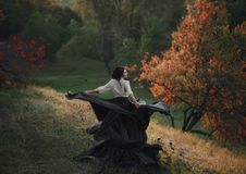 A girl in a vintage dress. Splits into particles, like ash. Background wild nature. Artistic Photography Stock Photography