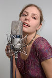 Girl with vintage microphone. Attractive young woman with retro microphone in sound room Stock Image
