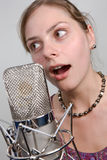 Girl with vintage microphone. Young attractive girl in audio studio Royalty Free Stock Images