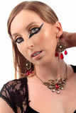 Girl vintage necklace earring. Girl in black dress with vintage earring and necklace with red transparent gemstone with heavy make-up on the eyes and black nails Stock Photos