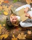 Girl in vintage outfit enjoy literature. Fall and autumn season. She likes detective genre. Girl blonde lay wooden. Background with leaves top view. Woman lady stock photos