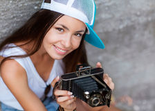 Girl with vintage retro camera. Girl with vintage retro camera having fun playful laughing. Multicultural Asian / Caucasian girl.Hipster style Royalty Free Stock Photography