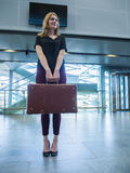 Girl with vintage retro suitcase in airport terminal Stock Photography