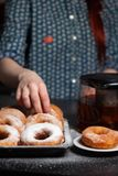 A girl in a vintage shirt with donuts, donuts on a plate, drzhit puffs in her hand, donuts in powdered sugar royalty free stock photo