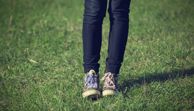 Girl in vintage sneakers resting on the grass Royalty Free Stock Photo