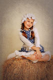 Girl in vintage style rustic sitting on a haystack. Girl in vintage style rustic sitting on a haystack Royalty Free Stock Image