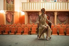 Girl in a vintage style sits in a retro dress on the stage of an empty theater. In the background, an empty auditorium Stock Images