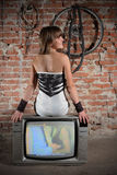 Girl on vintage TV receiver Royalty Free Stock Photos