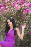 A Girl in a violet dress. A girl wearing a violet dress under the shade of a purple bouganville royalty free stock photos