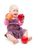 Girl in violet dress sits and holds red apples Royalty Free Stock Photography