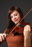 Girl with Violin. Young woman wearing a red sweater and holding a violin with dark background Royalty Free Stock Photography
