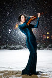 Girl with violin. Girl in green dress with violin on snow Royalty Free Stock Images