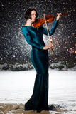 Girl with violin. Girl in green dress with violin on snow Stock Images