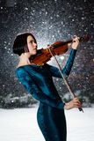 Girl with violin. Girl in green dress with violin on snow Stock Photography