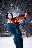 Girl with violin. Girl in green dress with violin on snow Stock Photo