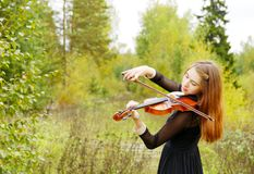 Girl with violin in the forest Stock Photography