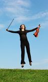 Girl with violin jumps on grass against  sky Royalty Free Stock Image