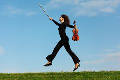 Girl with violin jumps on grass against sky Stock Photos