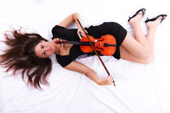Girl with violin laying on floor Royalty Free Stock Photos