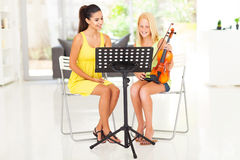 Girl violin lesson. Beautiful young pretty girl having violin lesson at home Stock Images