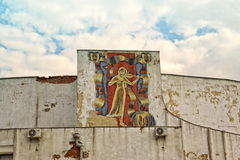 The girl with a violin, an old ruined mosaic on the building. Mosaic building destroy old girl violin art theater sky clouds wall Stock Photos