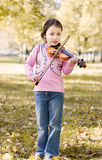 Girl with violin outdoor Stock Images