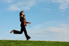 Girl with violin runs against sky, side view Stock Photos